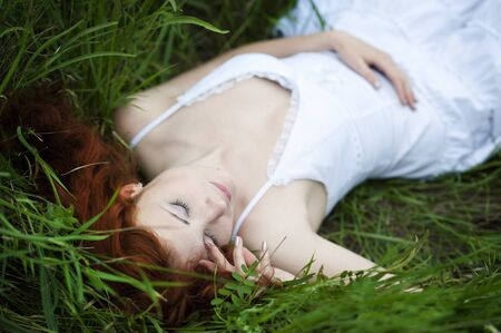 Young red hair woman portrait, lying in grass field Фото со стока - 130997703
