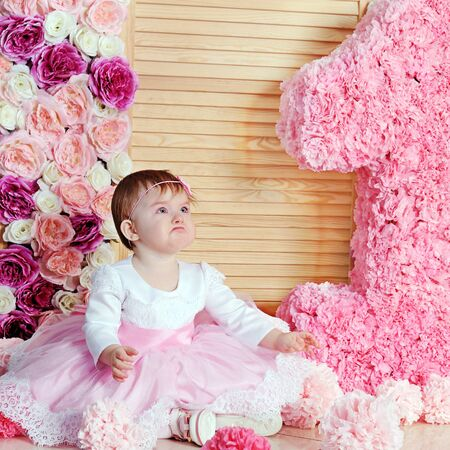 Cute upset baby girl in pink dress with her first birthday cake Фото со стока