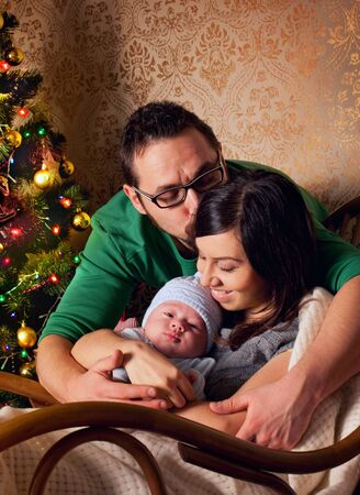 Family at home near christmas tree - woman, man and newborn baby