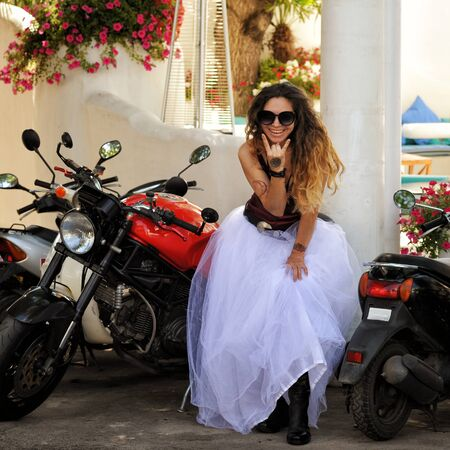 Happy bride woman posing with motorcycle, biker wedding, outdoors Stockfoto