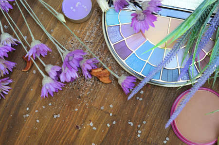 Flat lay eyeshadow palette and lavender flowers, wooden background with copy space for text