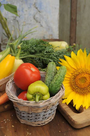 Summer vegetable frame made with sunflowers and assorted fresh vegetables on vintage wooden board, copy space for text
