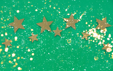 New Year ornaments, top view. Golden stars. Green background. Flat lay style. Festive picture with lightening golden bokeh lights. Stock Photo