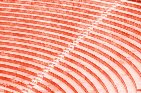 Old amphitheatre steps close up texture. Living coral colors. Color of the year 2019. Stock Photo