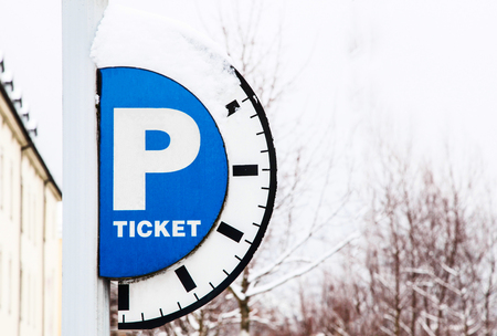 Blue parking sign with a big P, with inscription Ticket and with timeline on it on snow background