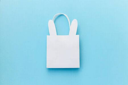 Paper bag with bunny on the blue background. Flatlay, top view, copy space.