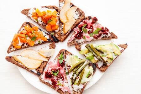 Assorted bruschetta with various toppings. Variety of small sandwiches. Mix bruschetta. Party concept. Banque d'images - 132080556