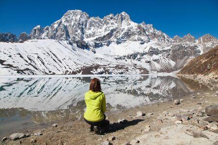 Girl trekker in yellow jacket enjoying view of mountain lake