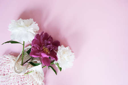 White and red peonies in a string-bag