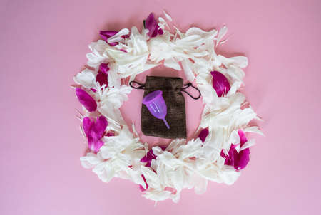 Purpure menstrual cup on the pink background with white and red peonies petals