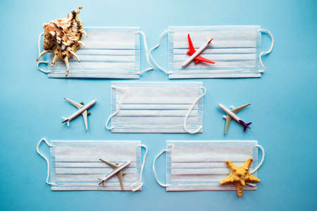 Medical masks, seashells and four planes on a blue background. Protection from COVID-19 concept. Flatlay. Top view. Stock Photo