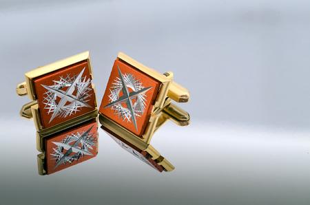 wrist cuffs: gold cufflinks on a mirrored reflective background