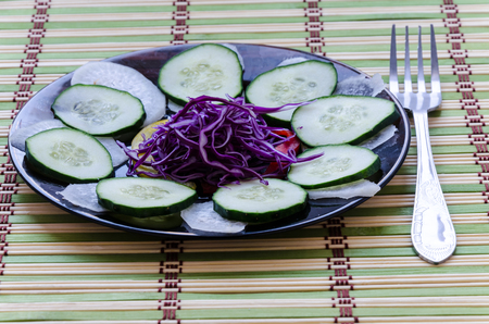 Recent sliced salad on a black plate