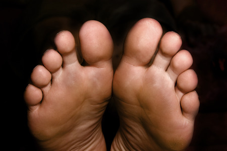 male parts: pair of feet on the black background