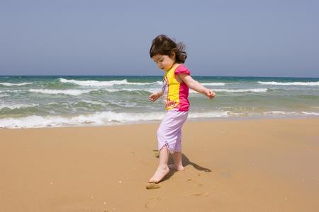 seacoast: The little girl plays on seacoast
