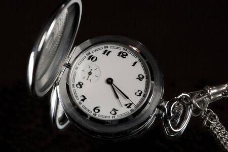Silver pocket watch on a black background photo