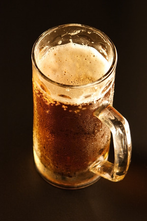 Mug with cold beer on a black background Stock Photo - 1686660