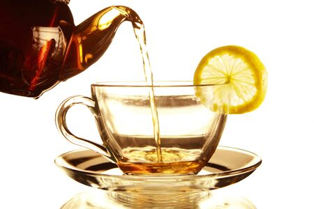 Teapot and glass cup of tea with lemon on a white background