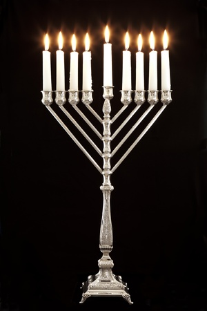Silver Hanukkah candles all candle lite on the traditional Hanukkah menorah