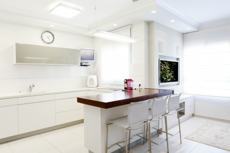 Modern design kitchen with white elements  Note to reviewer: Original picture in the TV Screens  was replaced by one of my images. Stock Photo