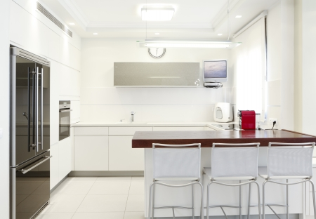 Modern design kitchen with white elements  Note to reviewer: Original picture in the TV Screen  was replaced by one of my images. Reklamní fotografie