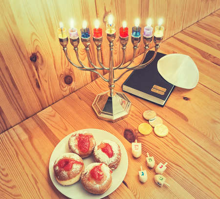 dreidels: Jewish Holiday Hanukkah With Silver Menorah (traditional candelabra) with Burning candles, Torah, Donuts And Wooden Dreidels,