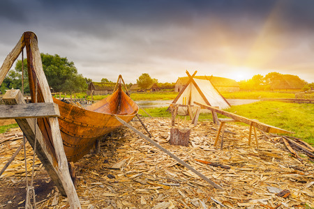 mediaval: Viking harbor with old boat in Denmark at sunset