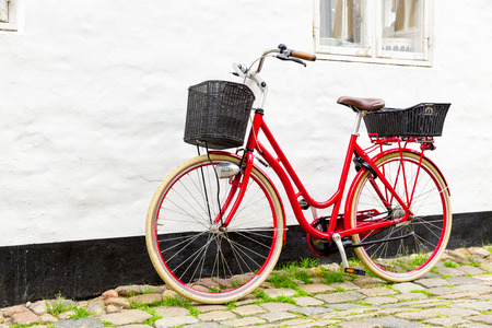 french way: Retro vintage red bicycle on cobblestone street in the old town. Ribbe, Denmark