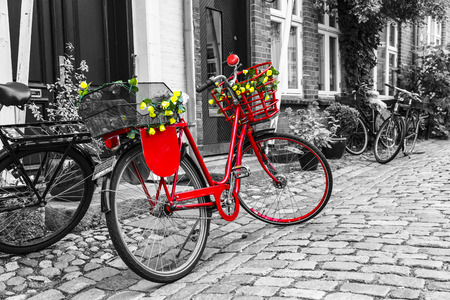 white color: Retro vintage red bicycle on cobblestone street in the old town. Black And White Toned. Ribbe, Denmark Stock Photo