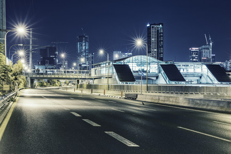 yom kipur: Empty freeway at night And Tel Aviv Cityscape in Background