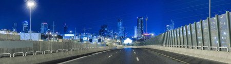 city road: Empty freeway at night And Tel Aviv Skyline in Background Stock Photo