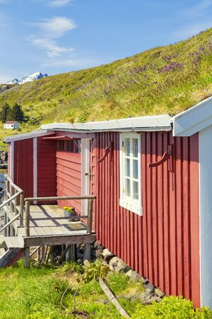 Part Of Red Classic Norwegian Rorbu fishing huts with sod roof on Lofoten islands, Norwegian traditional type of house used by fishermen Standard-Bild