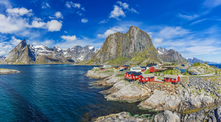 Reine On The Lofoten In Northern Norway. The Typical Norwegian Fishing Village Of Reine With The typical Rorbu Houses At Sunny Day, Mountain In Background