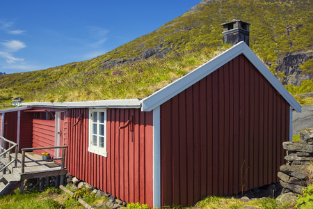 Red Classic Norwegian Rorbu fishing huts with sod roof on Lofoten islands, Norwegian traditional type of house used by fishermen