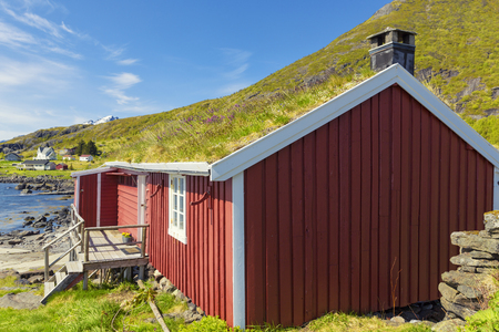 Red Classic Norwegian Rorbu fishing huts with sod roof on Lofoten islands, Norwegian traditional type of house used by fishermen Standard-Bild
