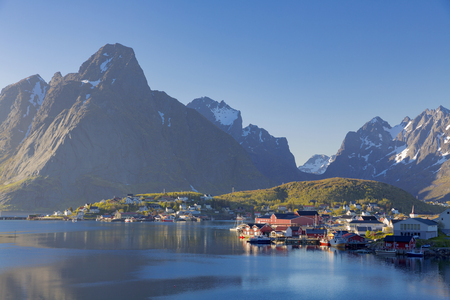 Island of Hamnoy, Reine on the Lofoten in northern Norway. The Typical Norwegian fishing village of Reine under midnight sun, blue sky, with the typical rorbu houses.  Mountain In Background Standard-Bild