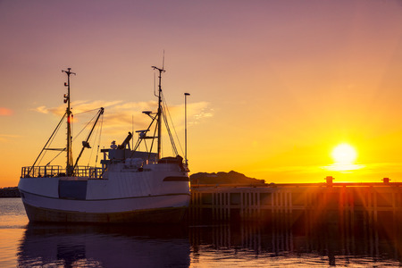 Fishing boats in harbor at midnight sun in Northern Norway, Lofoten Island, Ramberg, Norway - Mountain In Background
