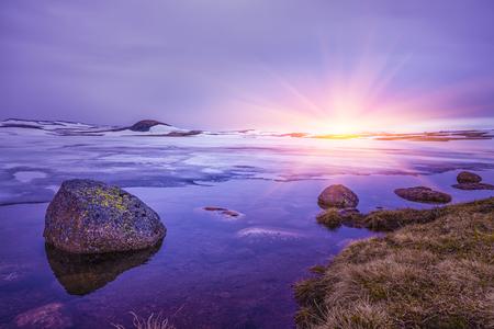 湖の岩の上に美しい日の出、湖で曇りの日、冬の風景、ノルウェー