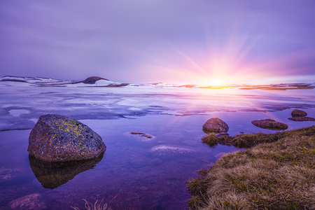 Beautiful sunrise over Rocks in a lake, An overcast day at the lake, Winter Landscape, Norway  Stock Photo