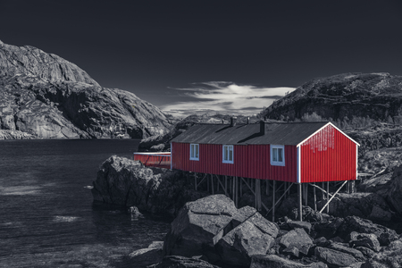 Red Classic Norwegian Rorbu fishing huts with sod roof on Lofoten islands, Nusfjord. Norwegian traditional type of house used by fishermen - Black And White Toned Standard-Bild