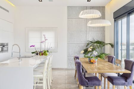 Modern Design Of Luxury White Kitchen With Marble Island And Dinner Table Foto de archivo