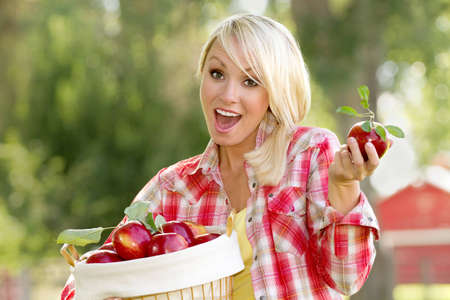 30 s: A Young blonde woman holding a basket of apples Stock Photo