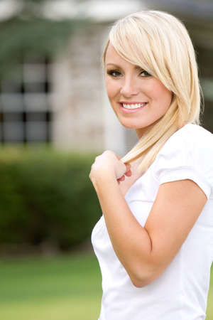 A young blonde smiling woman outside