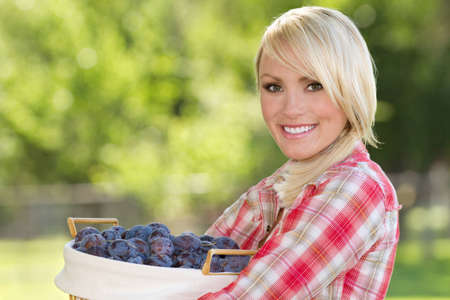 A young blonde woman holding a basket of plums Zdjęcie Seryjne