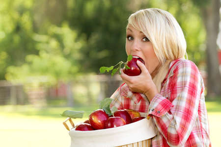A Young blonde woman holding a basket of apples Zdjęcie Seryjne