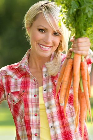 A blonde farm girl holding carrots