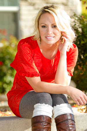 A young blonde woman sitting outside