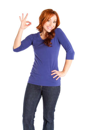 A red headed woman making an OK gesture.