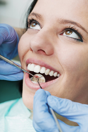 scaler: Young beautiful woman getting teeth cleaned by dentist