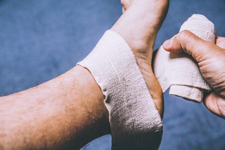 pies masculinos: Deporte lesiones tiro. esguince de tobillo. Un vendaje de la pierna tensor se aplica al aire libre. Cerrar hasta Shot Foto de archivo